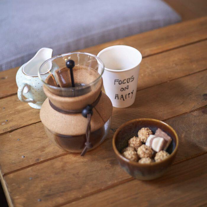 Kaffeekanne mit Becher und kleinem Snack auf Holztisch