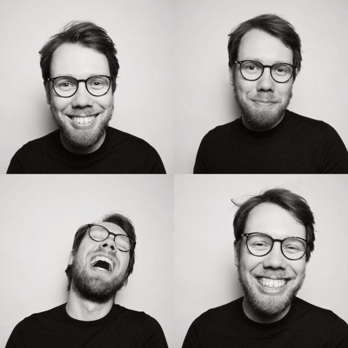 Bastian Schroeder vor weißem Hintergrund lacht in die Kamera