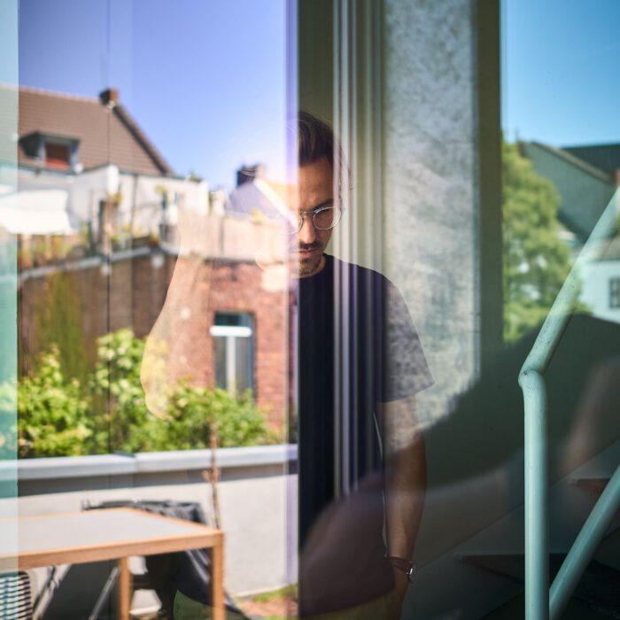 Mann grübelnd hinter der Reflektion einer Glasscheibe