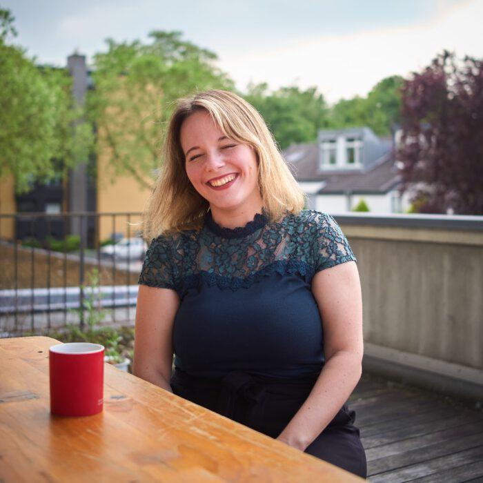 Jessica Rosenthal lacht beim Sitzen vor einer SPD Kaffeetasse